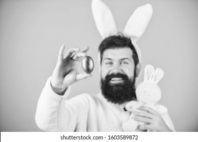 My precious. Hipster cute bunny long ears blue background. Easter bunny. Having fun. Funny bunny with beard and mustache hold pink egg. Easter symbol concept. Bearded man wear silly bunny ears.