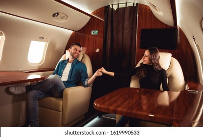 My significant other. A happy man is holding hands with his charming girlfriend and affectionately looks in her eyes while sitting in an aircraft cabin of a private jet.