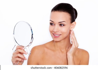 My skin feels great. Shot of a beautiful young woman looking at herself in small mirror over white isolated background