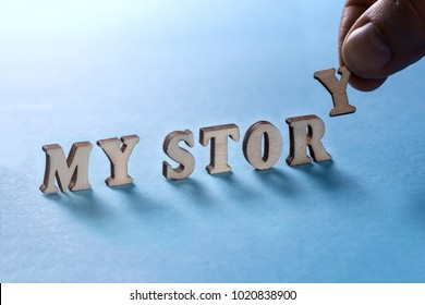 MY STORY from wooden letters on a blue background, a man's hand holds a letter Y