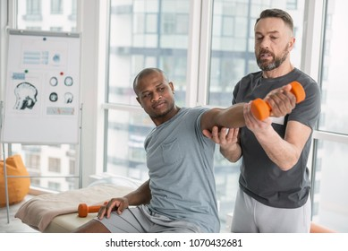 My strength. Nice pleasant man looking at his hand while lifting dumbbells