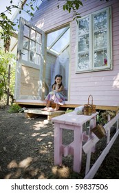 My sweet home. Little girl in her wood house for playtime.