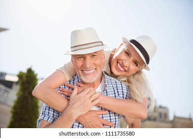 My sweetheart! Portrait of cheerful positive couple with beaming smiles in straw hats, attractive man carrying on back charming woman, enjoying time together outdside