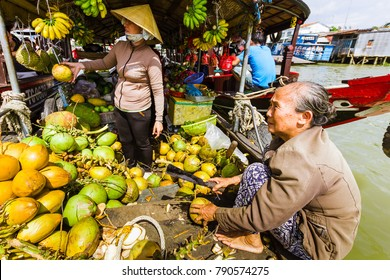 My Tho, Vietnam - January 04, 2016: two women selling coconuts and other fruits on a boat on the Mekong River in My Tho, Vietnam.