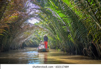 My Tho, Vietnam - March 1, 2017 : Tourist at boat at Mekong River Delta jungle cruise, Mekong Rivier , Unidentified famers are rowing on flooding lotus field in Mekong delta, Vietnam