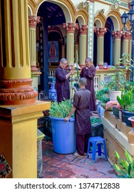 My Tho, Vietnam - March 9, 2019 :  Monks arranging flowers in courtyard at Vinh Trang Pagoda in My Tho, Vietnam.