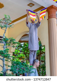 My Tho, Vietnam - March 9, 2019 :  Monks hanging banners in courtyard at Vinh Trang Pagoda in My Tho, Vietnam.