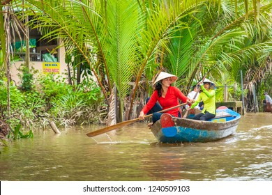 MY THO, VIETNAM - NOVEMBER 24, 2018: Vietnamese women in the traditional Vietnamese cap paddle a small boat with tourists on the Mekong River in My Tho city (in the Mekong Delta region of southern Vie