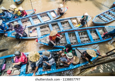 My Tho, Vietnam, Sep 10, 2017: aerial view, tourist in wood sampan boat when farmer is rowing on muddy river at Mekong Delta jungle cruise, the most popular tourist attraction around Ho Chi Minh City.