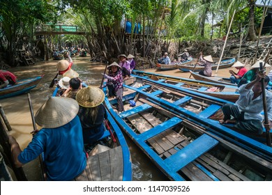 My Tho, Vietnam - Sep 10, 2017 : Farmers in wood sampan boat waiting tourist rowing on muddy river at Mekong Delta jungle cruise, the most popular attraction for the tourists around Ho Chi Minh City.