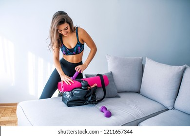 My way for healthy life. Young woman packing sports stuff for training into bag in living room. Space for text. Young woman and sports bag with gym equipment. Ready for sport training