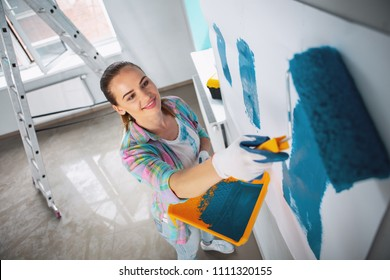 My weekend. Alert dark-haired woman holding a roller and painting the walls