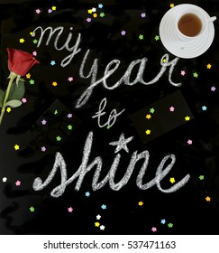"""My year to shine"" is a positive message handwritten with chalk on a blackboard with tea and a red rose."