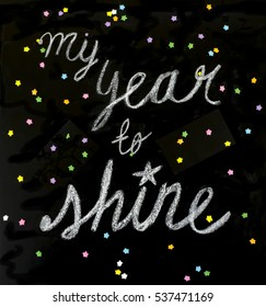 """My year to shine"" is a positive message handwritten with chalk on a blackboard."