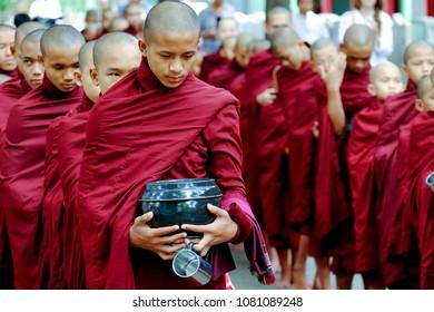 MYANMAR, AMARAPURA - JUNE 28, 2015: Buddhist monks queue for lunch in front of Mahagandayon monastery on 28 June 2015 in Amarapura.
