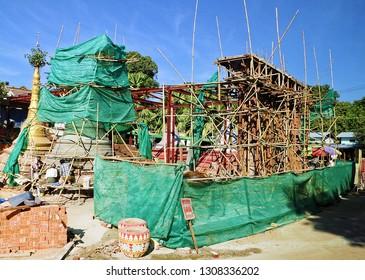 Myanmar - December 29, 2017: Burmish men are repairing local pagoda by sitting in the wooden shelves
