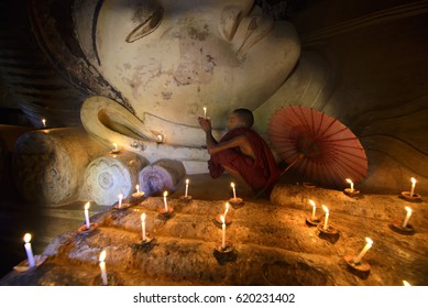 Myanmar - December 5, 2015 : A Little Buddhist Novice praying in front of Buddha Statue in Pagoda with candle lights, Bagan, Myanmar