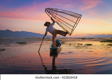 MYANMAR - DECEMBER 6 : Inle Lake on December 6, 2014 in Myanmar - AN unidentified fisherman is fishing with fishing net at Inle lake in the evening twilight time