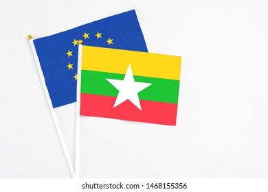 Myanmar and European Union stick flags on white background. High quality fabric, miniature national flag. Peaceful global concept.White floor for copy space.