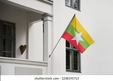 Myanmar flag hanging on a pole in front of the house. National flag waving on a home displaying on a pole on a front door of a building and raised at a full staff.