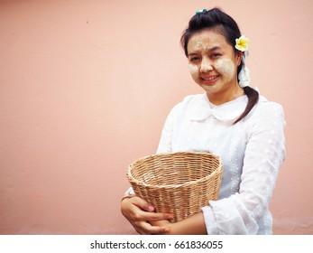 Myanmar girl with basket on pink background, Myanmar woman concept