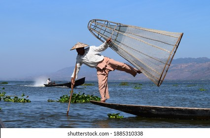 MYANMAR, INLE LAKE - JANUARY, 22, 2020: Fisherman Nyi Nyi is fishing on Inle lake, holding the wooden net and the stick, keeping the balance on his boat.