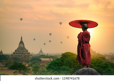 Myanmar Novice monk holding umbrella standing on the pagoda watching pagoda in Bagan sunrise morning time of Bagan Mandalay Burma