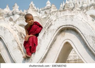 Myanmar The novice monk sitting on the white pagoda at Bagan Mandalay Burma