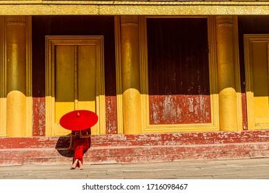 Femme birmane en costume traditionnel rouge tenant un parapluie rouge assise sur joli fond doré et porte en bois