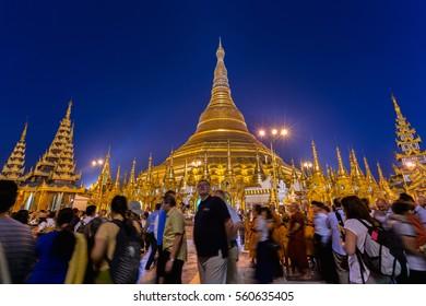 MYANMAR, YANGOON - JANUARY 15, 2017: Walking people in Shwedagon pagoda in Yangon, Myanmar. Shwedagon Pagoda is the most sacred Buddhist pagoda for the Burmese.