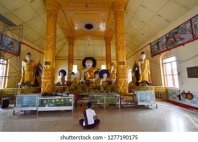 Myanmar, Ye. December 07, 2018 : Burmese woman prays in front of Buddha statues in the She San Daw pagoda.