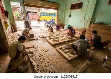 Myawaddy, Myanmar - July 01, 2018 : Unidentified Myanmar workers carving teak wood in complexity pattern at Myawaddy, Myanmar.