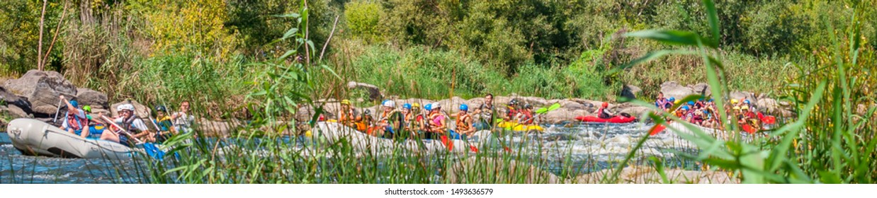 Myhiya, Ukraine - August 17, 2019: Rafting trip. A flotilla of several large inflatable boats descends along a fast, stony river.