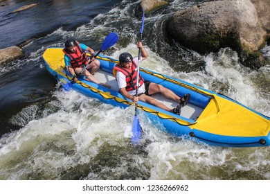 Myhiya / Ukraine - August 24 2018: Two man  white water kayaking on the river, extreme and fun sport at tourist attraction.  Rafting on the  Pivdennyi Buh River