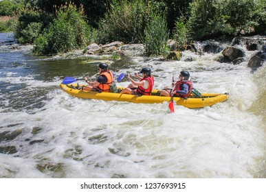 Myhiya / Ukraine - August 26 2018: three man  white water kayaking on the river, extreme and fun sport at tourist attraction.  Rafting on the  Pivdennyi Buh River
