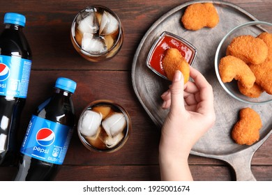 MYKOLAIV, UKRAINE - FEBRUARY 15, 2021: Woman eating fried chicken at wooden table with glasses and bottles of Pepsi, top view