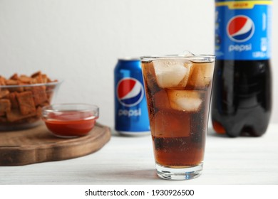 MYKOLAIV, UKRAINE - FEBRUARY 15, 2021: Glass of Pepsi and snack on white wooden table, space for text