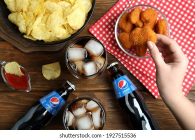 MYKOLAIV, UKRAINE - FEBRUARY 16, 2021: Woman eating chicken nuggets at wooden table with Pepsi, top view
