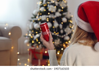 MYKOLAIV, UKRAINE - January 01, 2021: Woman in Santa hat with can of Coca-Cola against blurred Christmas tree at home, closeup