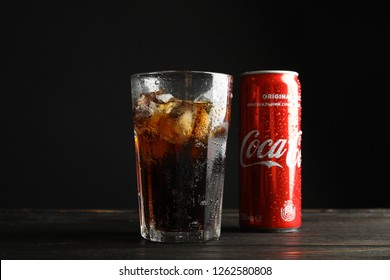 MYKOLAIV, UKRAINE - NOVEMBER 15, 2018: Glass and can with Coca Cola on table against black background