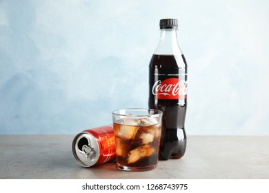 MYKOLAIV, UKRAINE - NOVEMBER 15, 2018: Bottle, glass and can with Coca Cola on table against color background