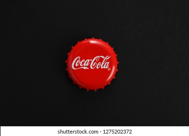 MYKOLAIV, UKRAINE - NOVEMBER 15, 2018: Coca Cola lid on black background, top view