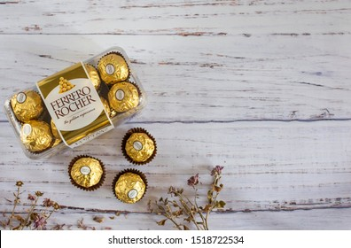 Mykolaiv, Ukraine - September 30, 2019. Ferrero Rocher - round chocolates. Candy in branded packaging, a sweet pleasure for children and adults on a wooden table with flowers.