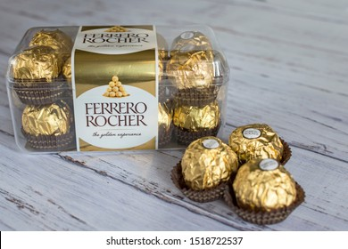 Mykolaiv, Ukraine - September 30, 2019. Italian chocolates Ferrero Rocher. A sweet and tasty start to the day for children and adults. Chocolate candies in gold foil, on a wooden background.