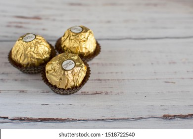 Mykolaiv, Ukraine - September 30, 2019. Ferrero Rocher chocolate and nut pastry balls on a wooden table. Each candy, packed in gold foil, contains 70 kilocalories.
