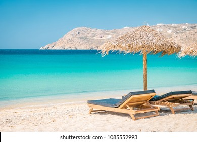 Mykonos beach during summer with umbrella and luxury beach chairs beds, blue ocean with mountain at Elia beach Mikonos Greece