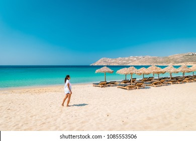 Mykonos beach during summer with umbrella and luxury beach chairs beds, blue ocean with mountain at Elia beach Mikonos Greece, Young woman on the beach in bikini swim wear