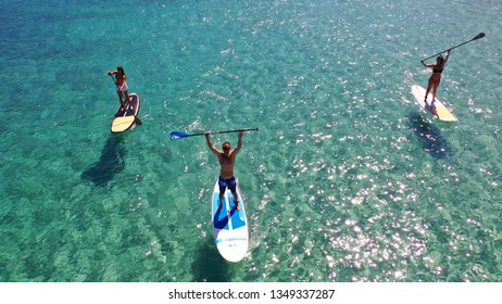 Mykonos, Cyclades / Greece - September 09 2018: Aerial drone photo of Stand Up Paddle board friends a fit man and 2 women practising SUP board in famous beach of Platy Gialos feeling happy