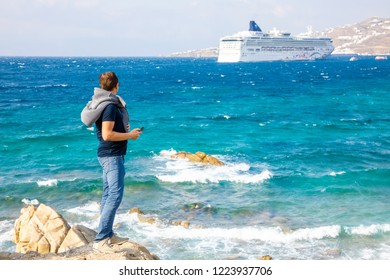 Mykonos, Greece - 17.10.2018: Young man looking on cruise ship, vacation at the colorfull town of Mikonos in Greece