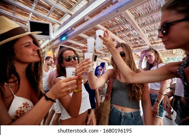 Mykonos, Greece 25 July 2015 Girls are  in the beach party and drinking Yeni Raki as a apéritif which is a sweetened, often anise-flavoured, alcoholic drink from Turkey. popular in Greece and Balkans